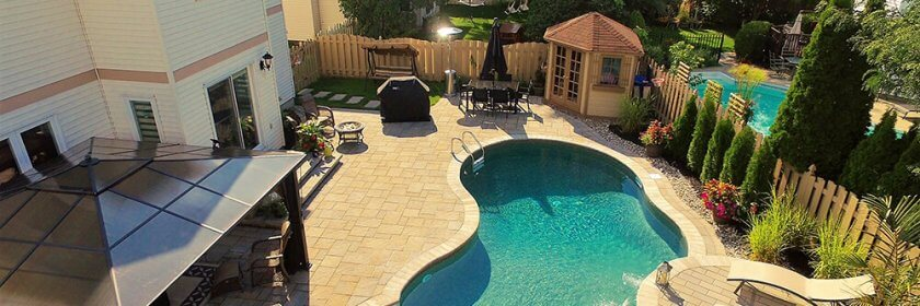 An aerial shot of a compact backyard pool and patio.