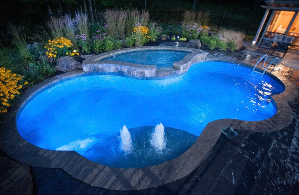 kidney bean shaped inground pool with attached hot tub spa and led lighting throughout