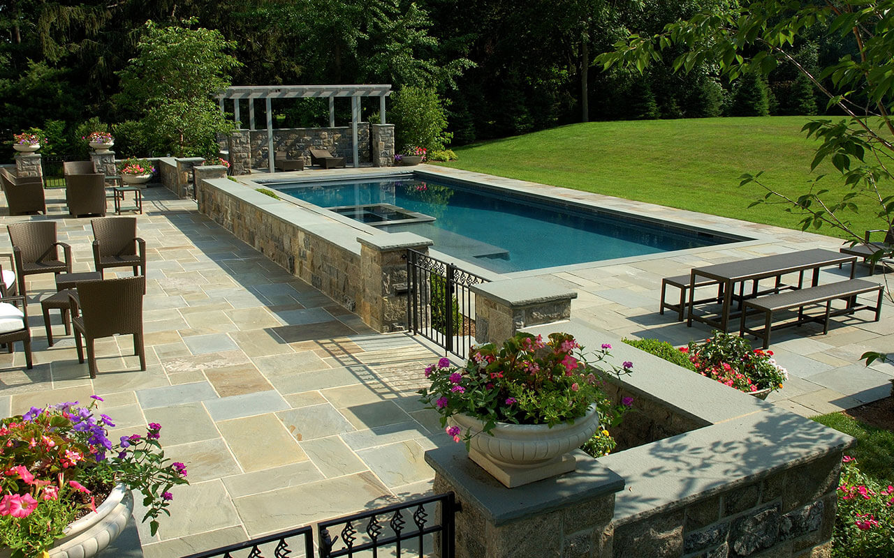 A contemporary pool with patio and landscaping, created by Edgewater Pools.