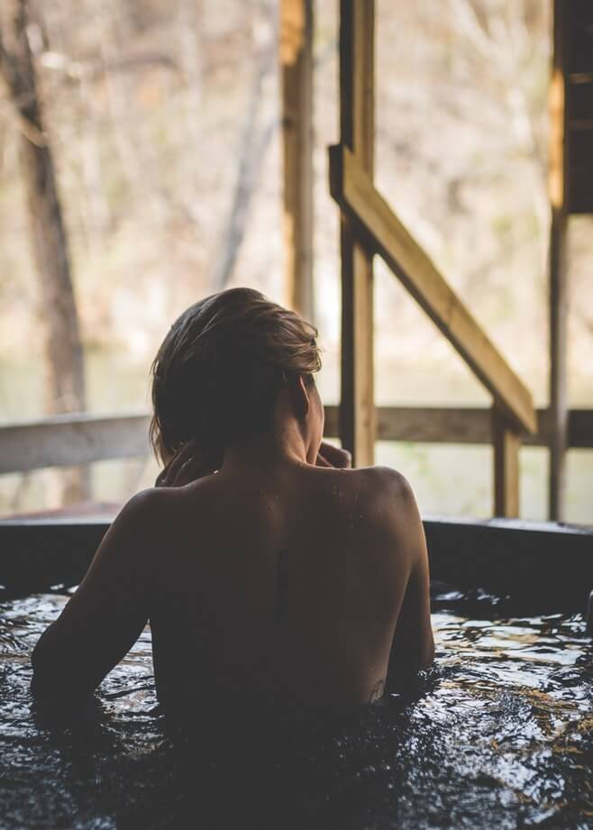 A woman looks out on her backyard from the comfort of a hot tub.
