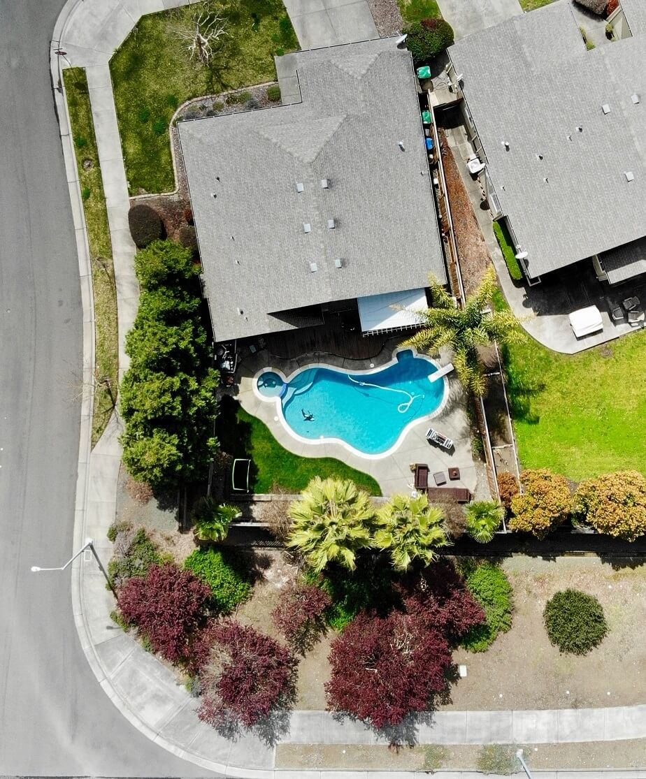 Aerial view of a home and backyard with a large pool and tropical trees.