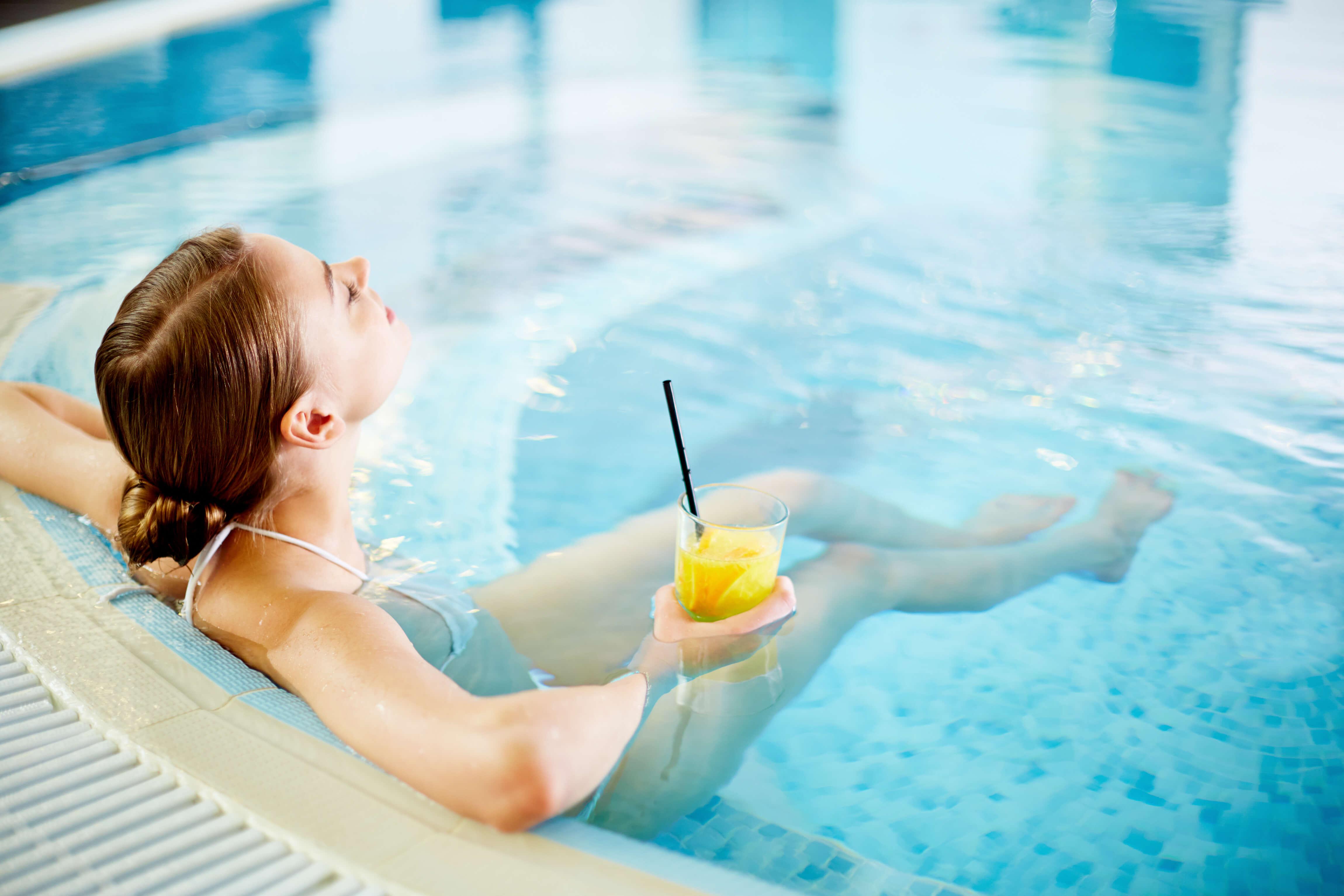 A woman enjoying a relaxing soak in a custom spa, drink in hand.