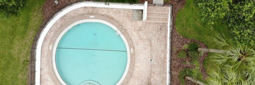 birds-eye view of circular inground pool with custom backyard landscaping