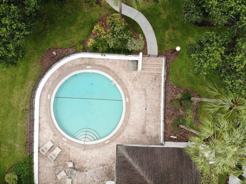 birds-eye view of circular inground pool with custom backyard landscaping
