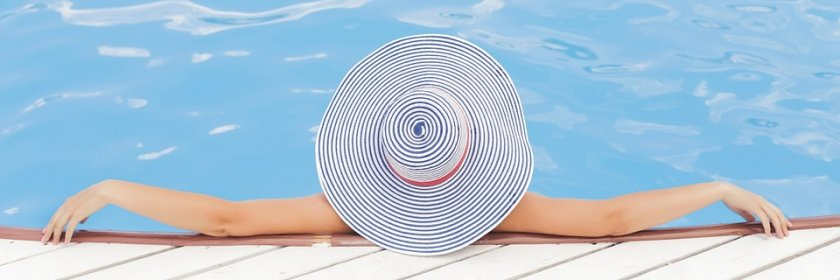 A woman in a sun hat reclines in a pool.