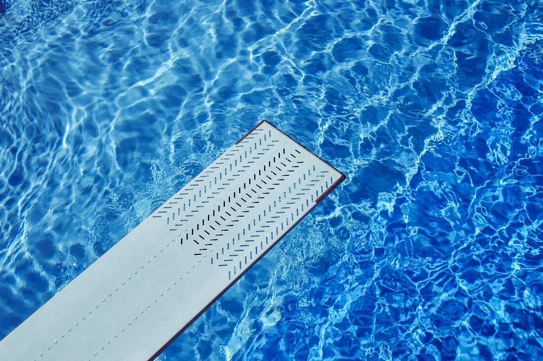 View of diving board above inground pool water
