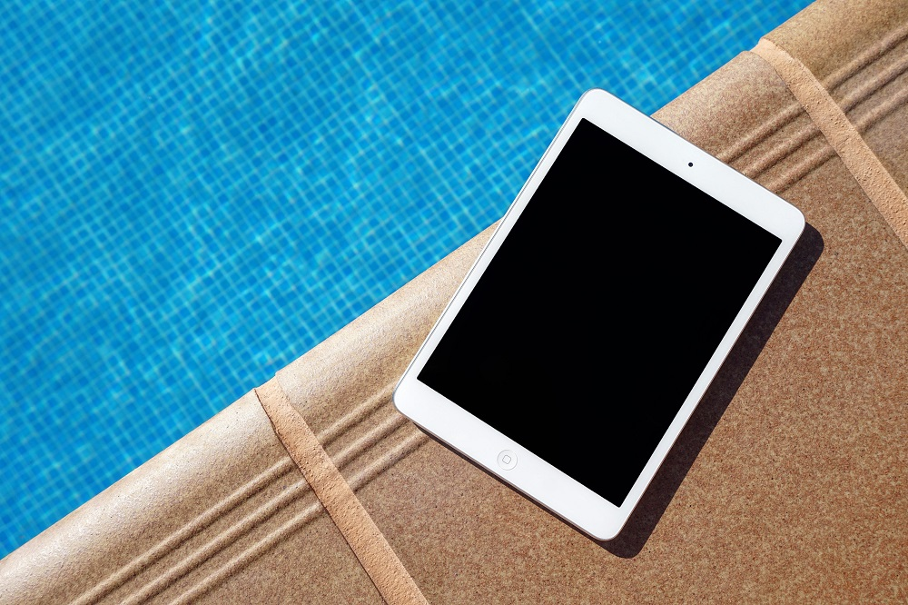 iPad sitting on the edge of a pool
