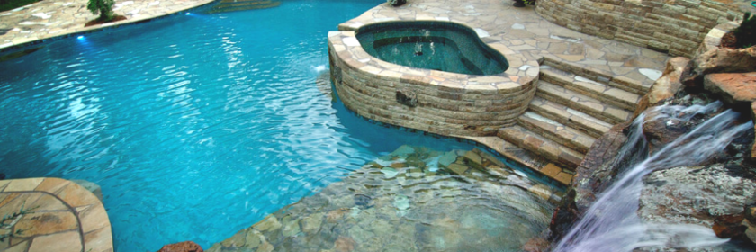 aerial view of luxury pool and spa in a unique shape with interlocking stone