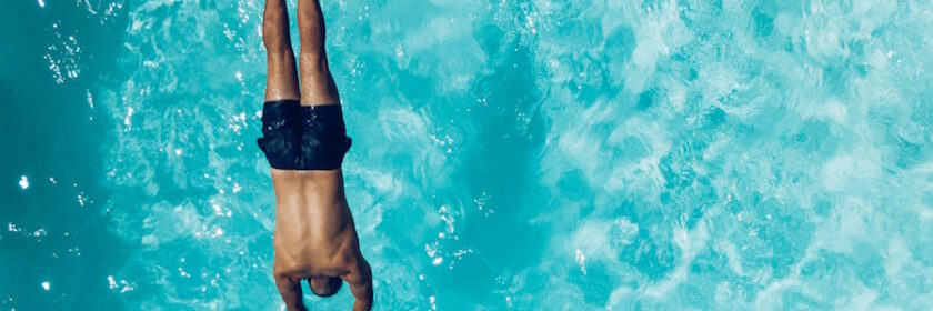Man in blue bathing suit diving into a swimming pool