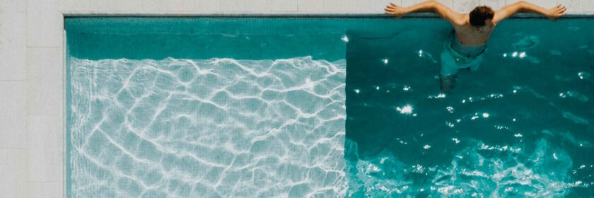 Man sitting at the end of a pool